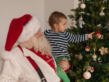 home decorating: Santa Claus with Child Decorating Christmas Tree at Home