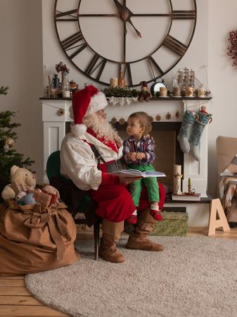 Kerstman met kind leesboek thuis Stockfoto