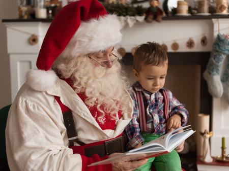 Santa Claus with Child Reading Book at Home Imagens