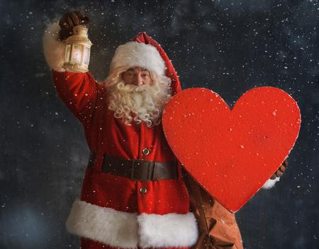 Foto van Santa Claus staat buiten onder de sneeuw en houden hart