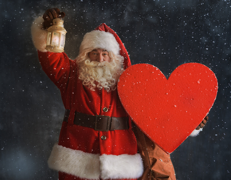 Photo of Santa Claus standing outdoors under snow and holding heart