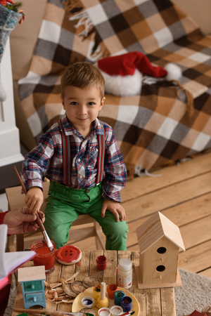 Santa Claus with Child making Christmas Gifts and Toys at Home