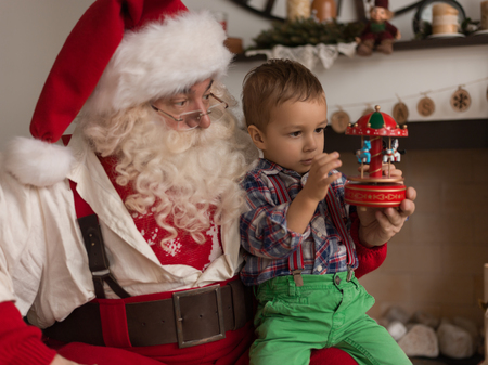 Santa Claus with Child Playing Together at Home Imagens