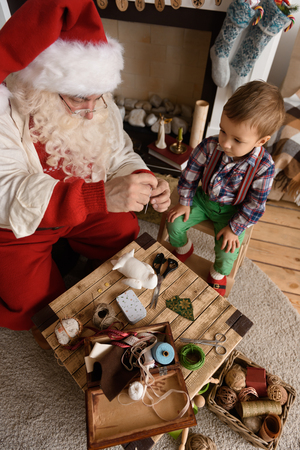 Santa Claus with Child sewing together at Home Imagens