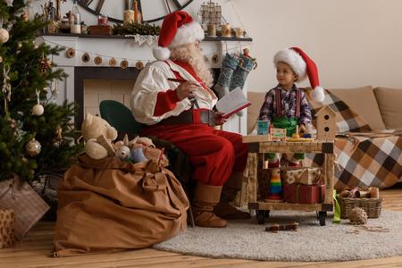 Kerstman met Kind het maken van Christmas Gifts en speelgoed thuis
