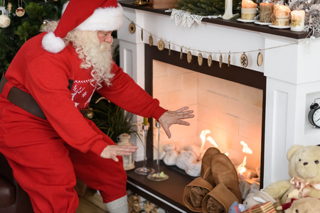 Santa Claus Warming near Fireplace at Home Imagens