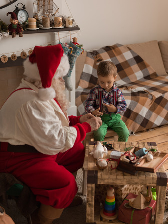 Santa Claus with Child sewing together at Home Standard-Bild
