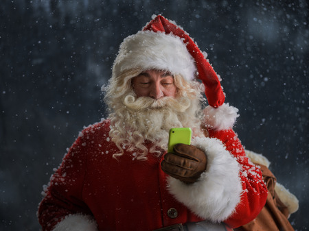 Photo of Santa Claus using mobile phone outdoors under snow