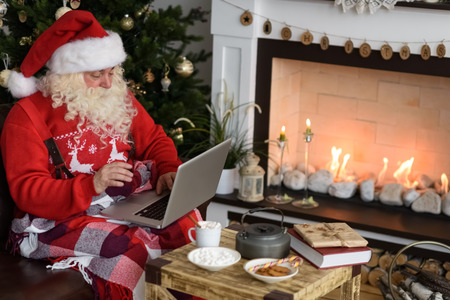 Santa Claus Working near Christmas Tree at Home. Reading childrens letters