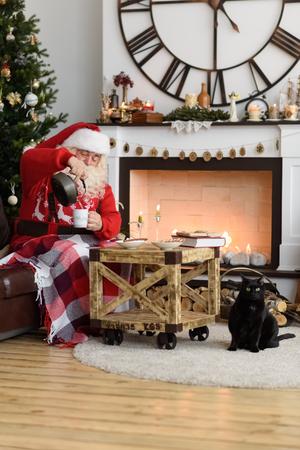 Kerstman koffie drinken met Marshmallow in de buurt van open haard thuis