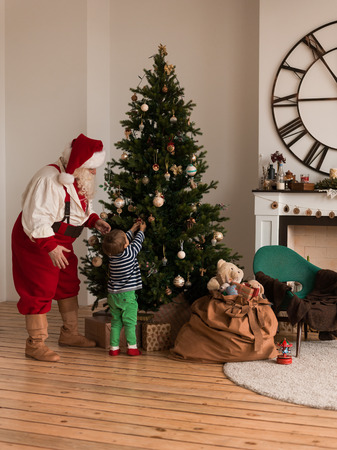 Santa Claus with Child Decorating Christmas Tree at Home