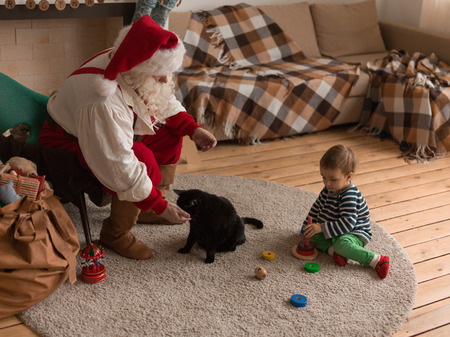 Santa Claus Playing at Home with Child and Cat Imagens