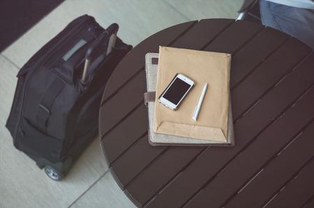 Business concept, smartphone, papier en pen op tafel op kantoor of luchthaven