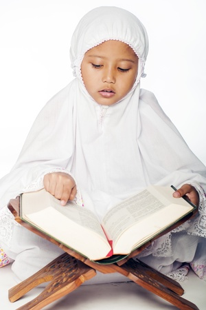 recite: A muslim girl wearing praying attire reading the holy quran