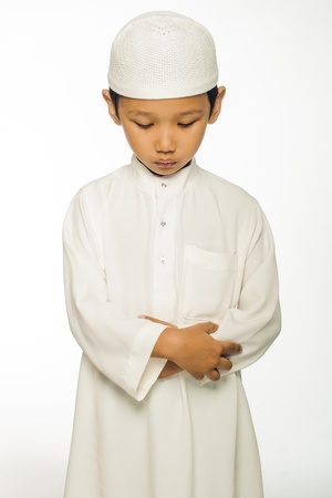 workship: A muslim boy wearing white islamic attire praying