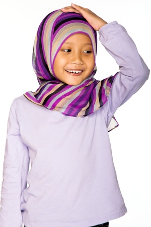 An Asian littel girl wearing head scarf wih a happy face photo