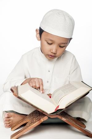 A little muslim boy wearing islamic attire reading the holy Quran
