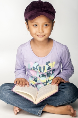 A Malay little girl with a purple book smiling at the camera photo