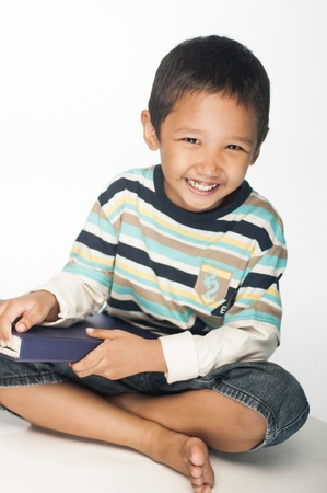 malay boy: A Asian boy holding a big book while laughing and looking at the camera