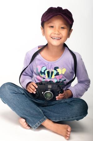 petite fille musulmane: Une jeune fille asiatique jouant avec un appareil télémétrique classique noir isolé sur fond blanc Banque d'images