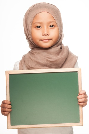 A Malay little girl wearing head scarf holding a blackboard photo