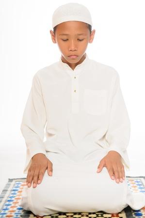 muslim pray: A praying muslim boy wearing islamic attire