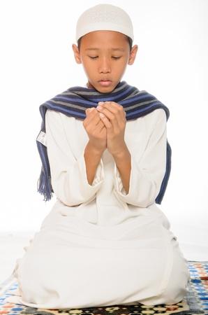 muslim pray: A muslim boy reading a Qoran and wearing islamic attire