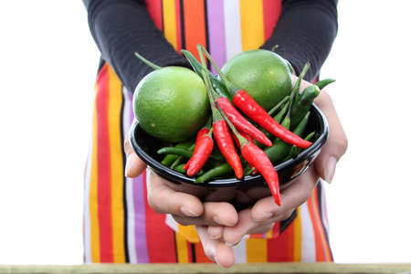 Women in colorful apron holding fresh red, green chili and lime in her hands�� photo