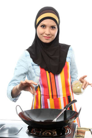 Action capture of a muslim female Chef adding spice on white photo