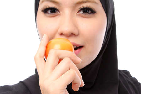 Close up Beautiful Young Muslim Woman Eating fresh Tomato.Dieting Concept.Vegetarian food on white photo