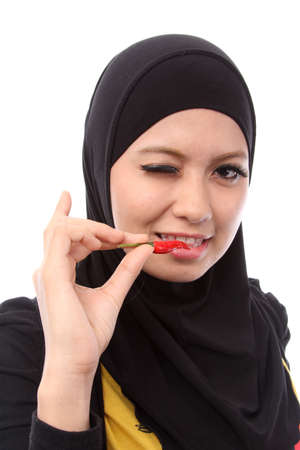 picture of lovely muslim woman with a hot fresh chilli on white photo
