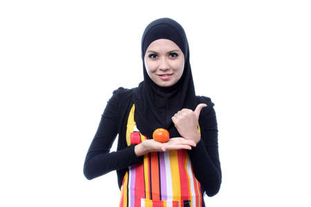 Young muslim shown tomato is good for health. diet concept on white photo