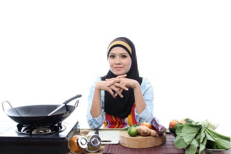femmes muslim: Les jeunes femmes musulmanes pr�tes � cuire avec le sourire sur fond blanc