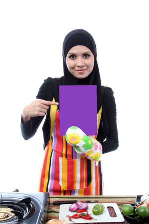 Young Muslim woman chef showing text Space photo