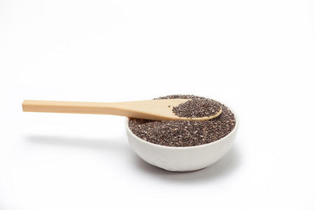 chia seeds in a white bowl with a wood spoon