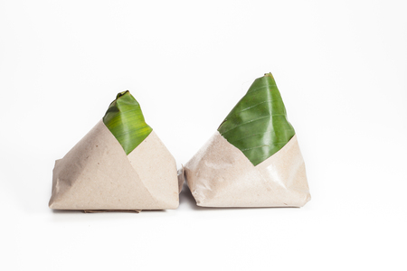 Tradisional malay food called Nasi lemak packed with banana leaf with brown paper