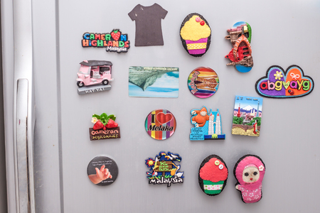 many different magnet souvenir on the fridge