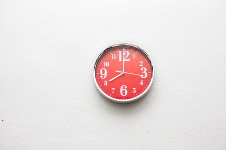 Red wall clock at  eight oclock on white wall