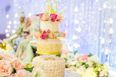 three tier decorated wedding cake over blurry wedding couple background