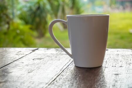 the mug on wooden  table over nature blurry background