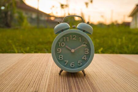 lite blue  analog clock over blurry sunset