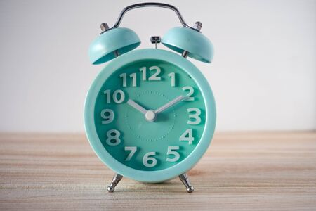 lite blue analog clock on wooden table