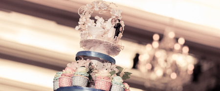 Doll or model bride and groomon top of wedding cake photo