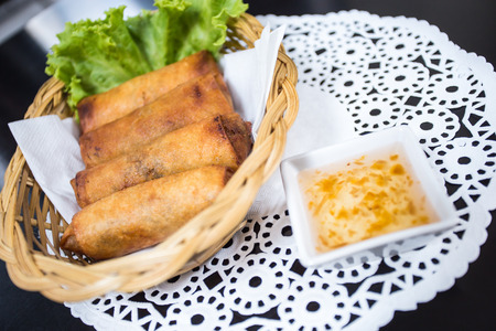 Fried Spring Rolls (Por Pia Tod) with sweet syrup sauce on black table photo