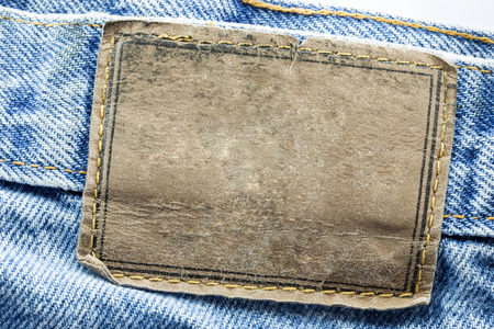 jeans fabric: Blank leather jeans label sewed on a blue jeans isolated on white background
