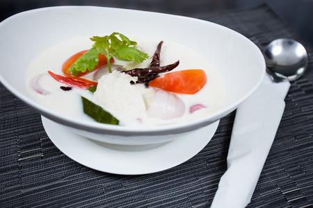Thai Chicken Soup in Coconut Milk in white bowl  photo