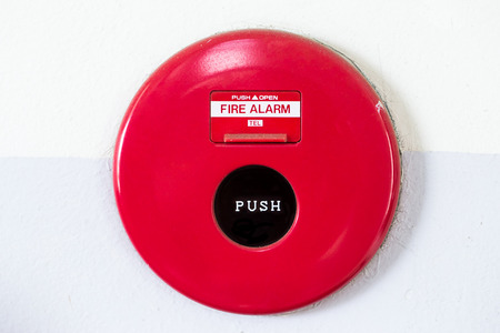 Red fire alarm on the wall photo