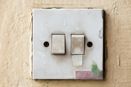 Old and dirty Light control switch on yellow background Stock Photo