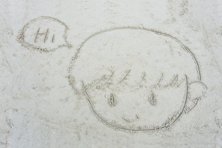 cartoon face of little boy drawn on the sand at beach photo