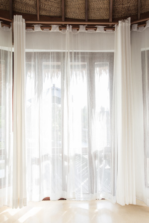 Light shines through white curtains in room Stock Photo